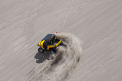 Yellow side by side buggy racing by in the sand dunes Royalty Free Stock Images