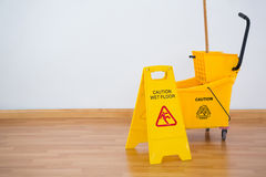 Yellow sigh boad with mop bucket on floor against wall Royalty Free Stock Photo