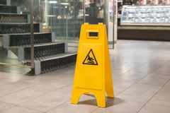 Yellow sign alerts for wet floor stock images