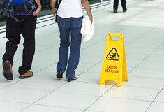 Yellow sign that alerts for wet floor. Stock Photos