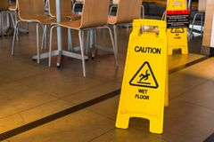 Yellow sign that alerts for wet floor in the restaurant.Thailand. royalty free stock image
