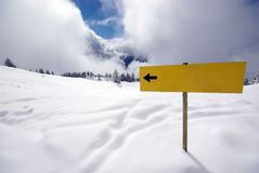 Yellow sign with arrow in mountains. Yellow sign showing way in mountains Stock Photo