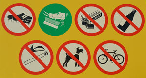 Yellow sign board next to a football field. This sign board indicates that it is forbidden to bring track spikes, chewing gum, alcoholic drinks, cigarettes, dogs Royalty Free Stock Photography