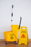 Yellow sign board with mop bucket on floor against wall Stock Photo
