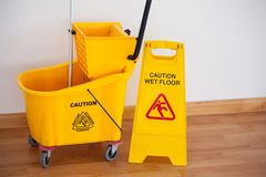 Yellow sign board with mop bucket on floor against wall Royalty Free Stock Photo