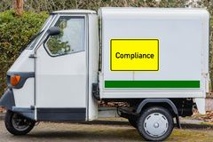 Yellow sign with Compliance on a delivery van royalty free stock photo