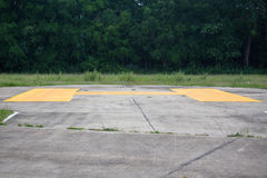 Yellow sign on concrete helipad Royalty Free Stock Image