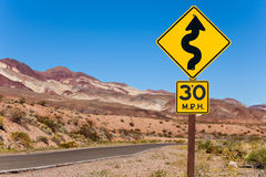 Yellow sign with curved arrow and road, California Royalty Free Stock Image