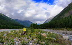 Yellow sign in line with the mountain river Stock Image