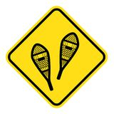 Yellow sign for snowshoeing route. Old style traditional snowshoes. winter outdoor activity Stock Images