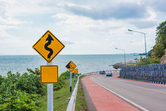 Yellow sign with winding road symbol in the countryside sea and sky background.  Stock Images