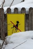 Yellow Signboard: a Signal Prohibiting Dog Excrements near Fresh Snow.  Royalty Free Stock Images