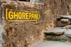 Yellow signpost arrow on the stone wall heading to Ghorepani on Poon Hill, Annapurna circuit trek, Nepal, Himalayas. Yellow signpost arrow on the stone wall stock photos