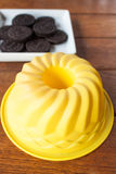 Yellow silicone cake form on wood table Stock Image