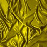 Yellow silk cloth with folds. Stock Photos