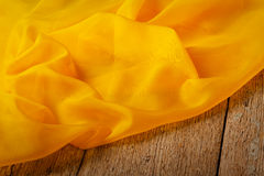 Yellow silk scarf. On wooden background Royalty Free Stock Photo