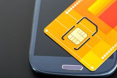 Yellow sim card on the phone Royalty Free Stock Photos