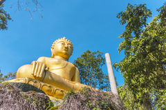 Yellow sitting Budha image with blue sky Royalty Free Stock Photography