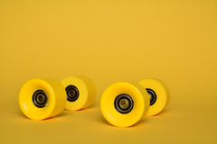 Yellow skate wheels. Four yellow rollerskate wheels on a yellow background Royalty Free Stock Images