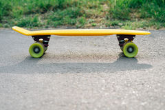 Yellow skateboard with green wheels on the pavement. Copy space Royalty Free Stock Photography