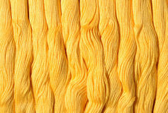 Yellow skeins of floss as background texture Stock Photos