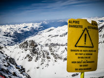 Yellow ski board with warning. Dangerous - yellow board with warning on the top of the mountain, Val Thorens, France Stock Photo