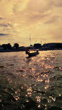 Yellow sky over Chaopraya River and small boat in strong waves Royalty Free Stock Image