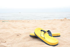 Yellow slippers on beach Royalty Free Stock Photo