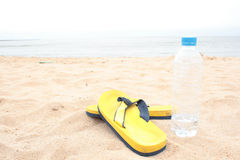 Yellow slippers on beach Stock Photography