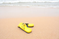 Yellow slippers on beach Stock Image