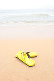 Yellow slippers on beach Royalty Free Stock Image