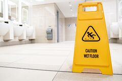 Yellow Slippery Warning Sign, Caution Wet Floor Sign In The Toilet Room Stock Photo