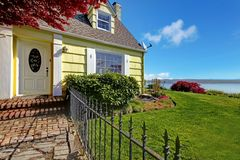 Yellow small classic home with water view and fence. Royalty Free Stock Photos