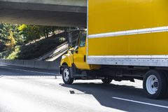 Yellow small size compact rig semi truck with box trailer transporting local commercial cargo driving on the road under. The bridge delivering commercial cargo stock image