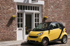 Yellow Smart Car. A bright yellow, tiny, Smart Car parked in front of a red brick building on a cobblestone street Royalty Free Stock Photography