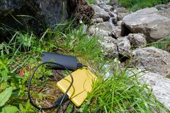 Yellow smartphone charged from a black external battery powerbank, placed on grass, near rocks, up in the mountain. Staying connected while hiking concept royalty free stock image