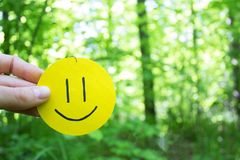 Yellow smile on green leaves background. Love to nature. positive emotions concept royalty free stock images