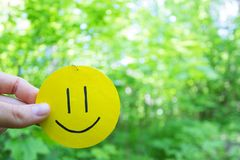 Yellow smile on green leaves background. Love to nature. positive emotions concept royalty free stock photo