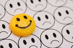 Yellow smiley against sad emoticon Royalty Free Stock Photography