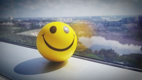 Yellow Smiley Ball Near Clear Glass Window Panel Royalty Free Stock Image