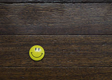 Yellow Smiley. Magnetic Yellow Smiley on a wooden background Stock Image