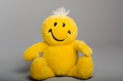 Yellow smiley, stuffed toy. Yellow smiley, positive stuffed toy for children on a gray background Royalty Free Stock Photos