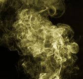 Yellow smoke against a black background. Photo of an abstract texture Stock Photos