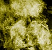 Yellow smoke on a black background. Photo of an abstract texture Royalty Free Stock Images