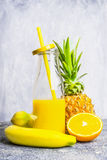 Yellow smoothie bottle with straw and ingredients on light wooden background, side view Stock Photos