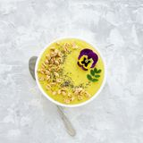 Yellow smoothie bowl with Chia seeds, air wheat and pansy flower on concrete background royalty free stock images
