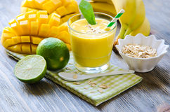 Yellow smoothie in glasses with mango, lime, rolled oats Royalty Free Stock Images