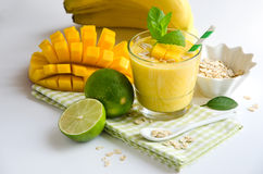 Yellow smoothie in glasses with mango and tropical fruits Royalty Free Stock Image