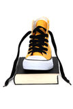 Yellow sneaker on black book Stock Photo