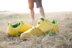 Yellow sneakers. On dry grass in field on legs background Stock Images